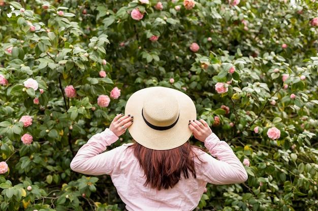 緑の小枝に成長しているピンクの花の近くの帽子の女