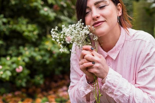 Довольная девушка с белыми цветами в парке