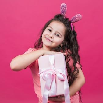 Милая девушка в ушах зайчика с подарочной коробкой