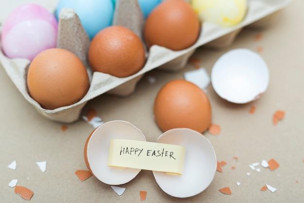 割れた卵の紙の上のハッピーイースターの碑文