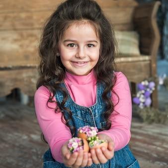 花と壊れた卵を持って幸せな女の子