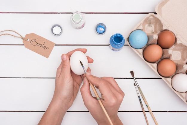 Человек рисует яйцо на пасху кистью
