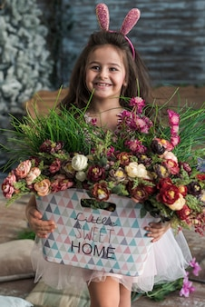 Счастливая девушка в ушах зайчика с цветами в сумке