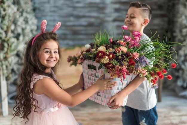 バニーの耳の中の女の子に花を持つバッグを与える少年