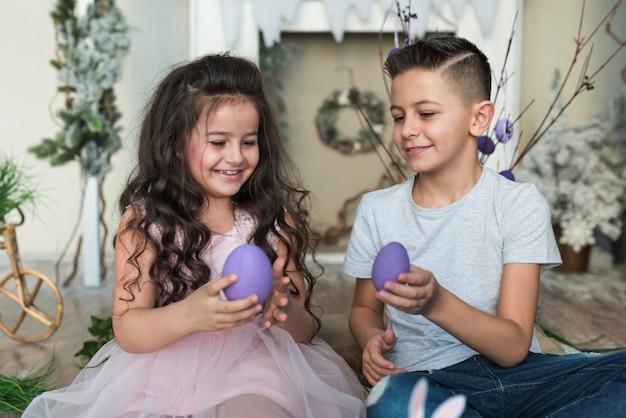 男の子と女の子のイースターエッグと一緒に座って
