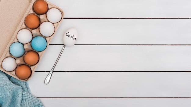 スプーンで白い卵のイースター碑文