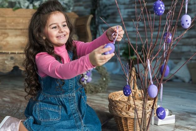幸せな女の子の枝にイースターエッグをぶら下げ