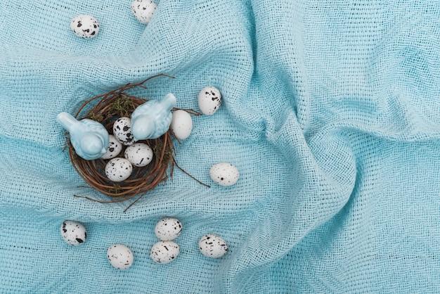 青い布の上の巣でウズラの卵