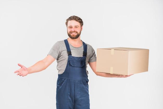 大きな箱で立っている陽気な配達人