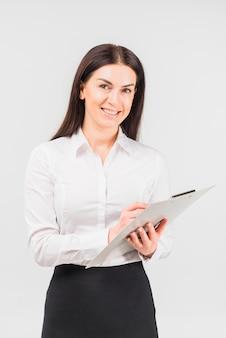 Счастливая бизнес-леди стоя с доской сзажимом для бумаги