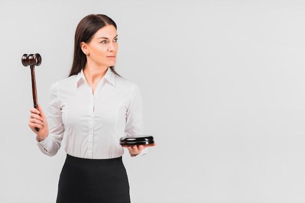 小槌を手で押し女性弁護士