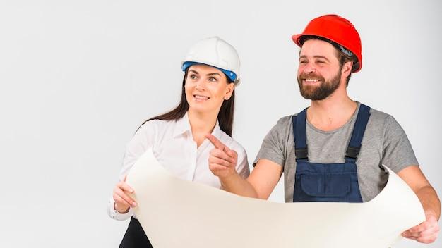 女性エンジニアとビルダーの指を指すプロジェクトを議論します。