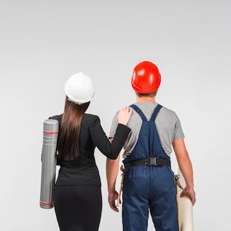 Женщина инженера стоя с строителем