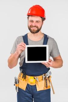 Ремонтник в целом держа планшет с пустым экраном