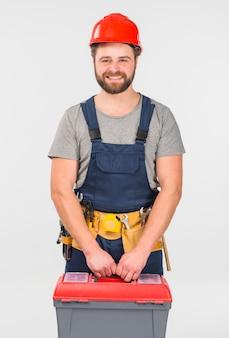 Ремонтник в общем с ящиком для инструментов улыбается