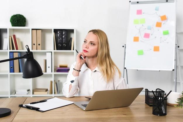 オフィスで木製のテーブルの上のラップトップと考えている若い実業家