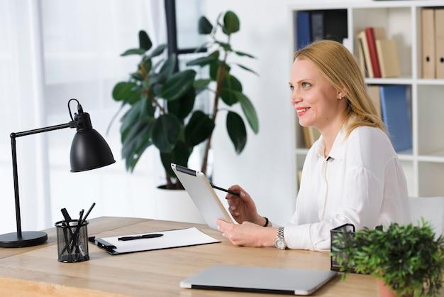 Усмехаясь белокурая молодая женщина сидя на рабочем месте используя цифровую таблетку