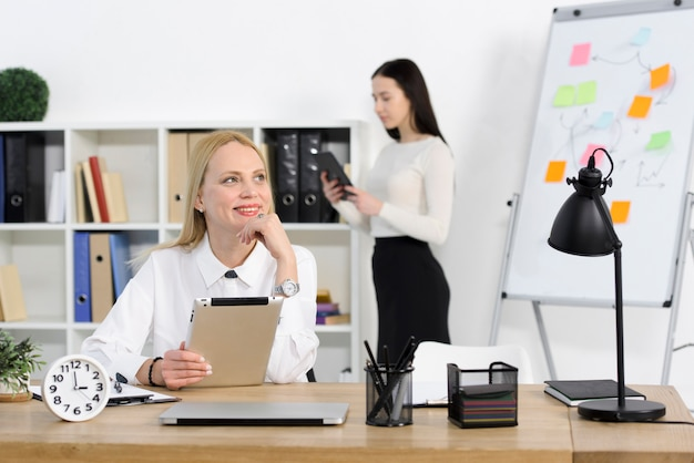 Портрет улыбающегося молодой предприниматель, проведение цифровой планшет, глядя с ее коллегой, стоя на фоне