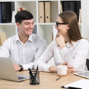 ビジネスマンやビジネスウーマンがお互いを見て職場で一緒に座っています。