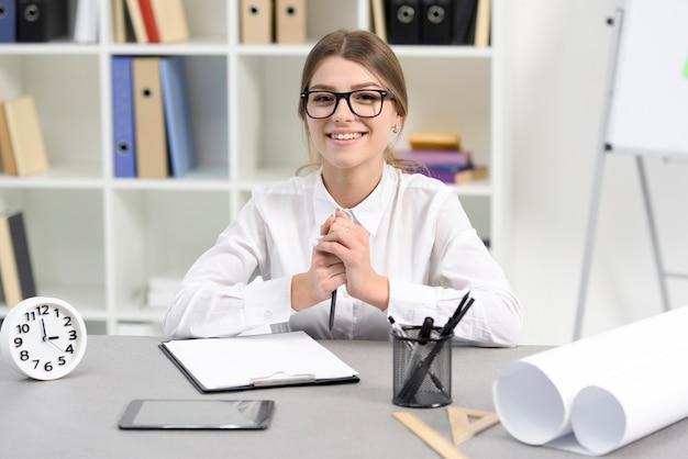 クリップボードで職場に座っている笑顔若い実業家の肖像画。目覚まし時計;机の上の携帯電話と鉛筆ホルダー