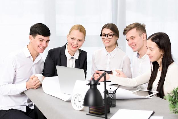 Группа бизнесменов обсуждают проект на ноутбуке