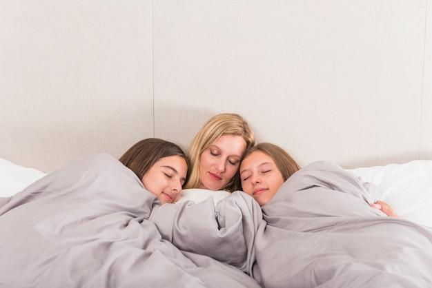 Мать и две милые дочери спят в постели