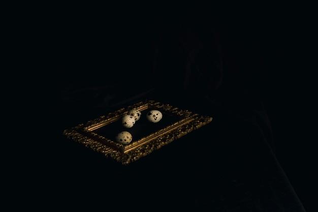 黒さの間のフォトフレームにウズラの卵