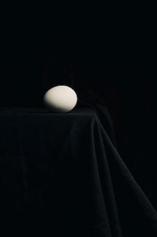 黒さの間にテーブルの端に鶏の卵