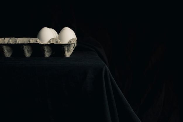 黒さの間にテーブルの端にコンテナー内の鶏の卵