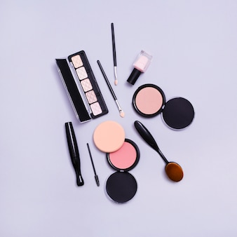 Палитра теней для век; макияж кисти и компактная пудра на фиолетовом фоне