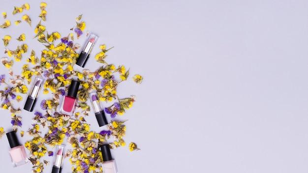Желтые и фиолетовые цветы с красочными помадами и розовым лаком для ногтей на цветном фоне