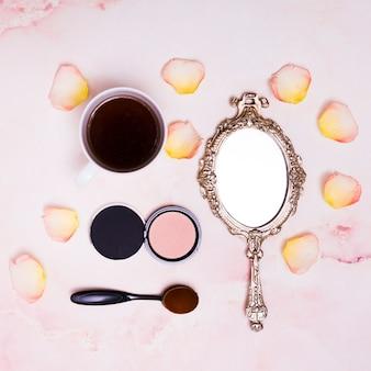 Чашка кофе; лепестки; компактная пудра; овальная кисточка и компактная пудра на розовом фоне