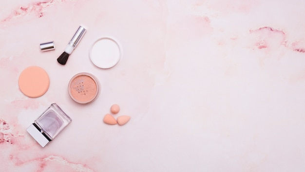 Пудра для лица; косметическая кисточка; пуховка; бутылка и блендер на розовом фоне