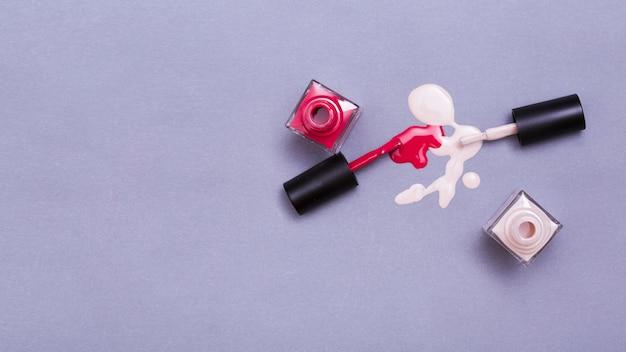 Пролитая бутылка красного и розового лака для ногтей на фиолетовом фоне