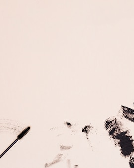 ベージュ色の背景にマスカラーのまつげブラシストローク