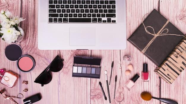 化粧品とピンクの木製の織り目加工の背景に日記とノートパソコン