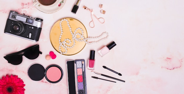 ヴィンテージの古いカメラ。サングラス;ガーベラの花。スポンジ;ネックレス;ピンクの背景に化粧品