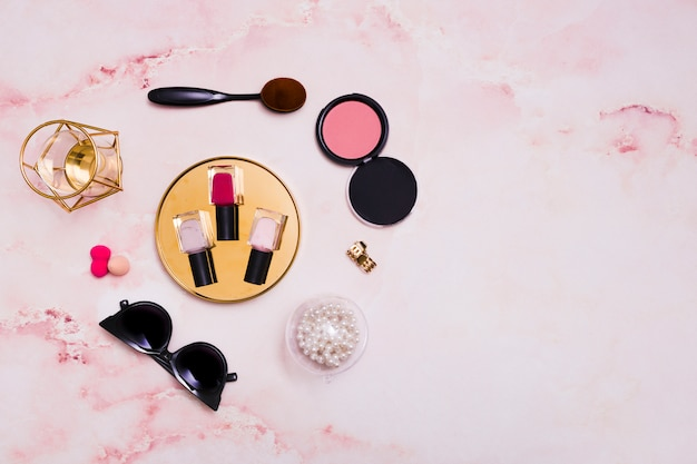 Флаконы для лака для ногтей; ожерелье; солнцезащитные очки; губка; овальная кисточка для макияжа на розовом фоне