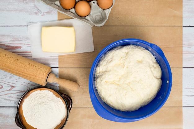Замесить тесто в синей миске; яйца; сливочное масло; мучной; и скалка на деревянный стол
