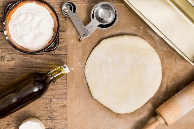 Свежее тесто готово для выпечки на пергаментной бумаге с мерными ложками; мучной; масло и скалка над деревянным столом