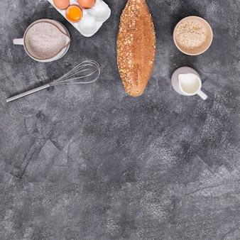 卵;ミルク;ひげ;一斤のパン。コンクリートの背景に小麦粉とオート麦ふすま