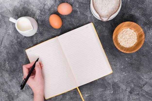 Крупный план человека, пишущего в дневнике с ингредиентами хлеба на бетонном фоне