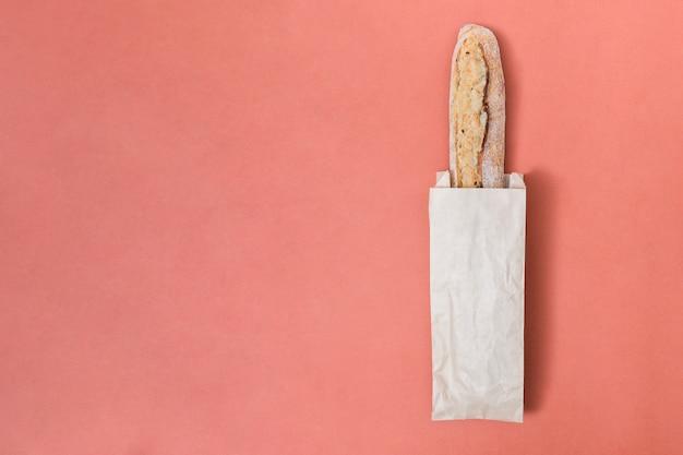 色付きの背景上の紙袋にバゲットのパン