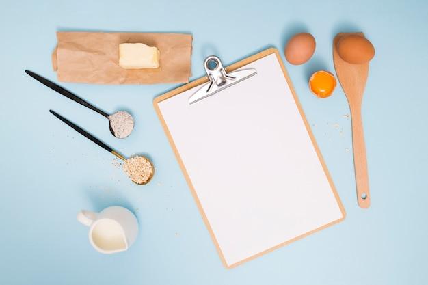 バター;卵;小麦粉;麦ふすまと青い背景上のクリップボードと牛乳