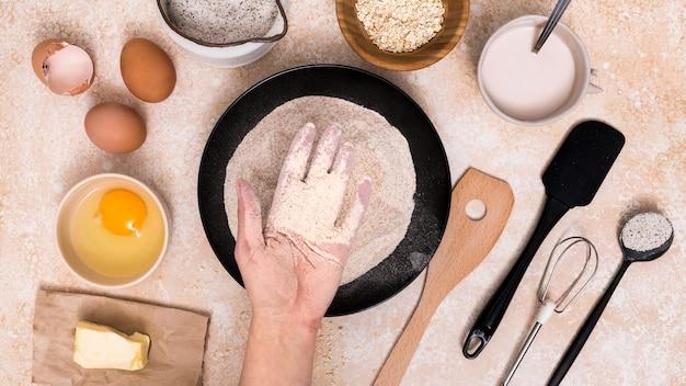 Человек, показывая муку в тарелку с хлебом ингредиенты на фоне