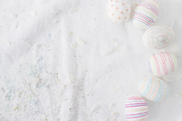 Коллекция пасхальных яиц с узорами возле перьев на текстиле