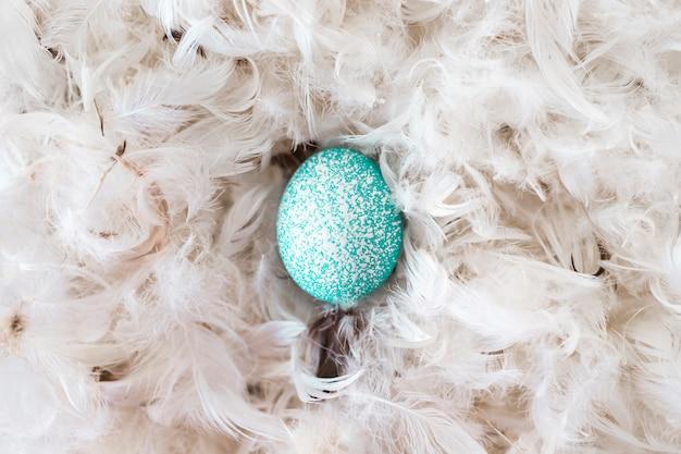 羽根の山の間の青い鶏の卵