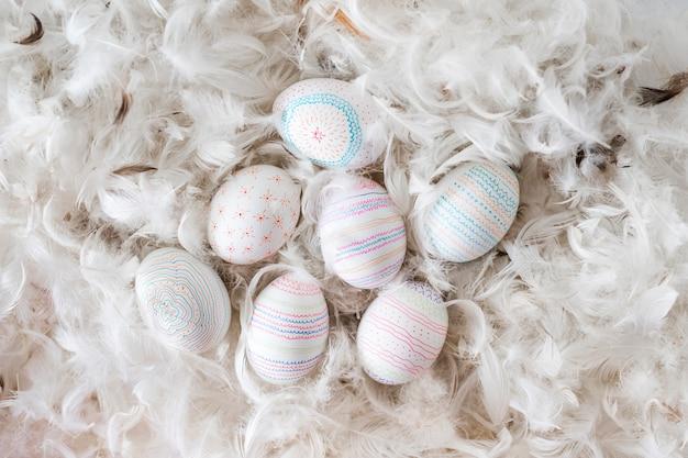 羽のヒープ間の鶏の卵のコレクション