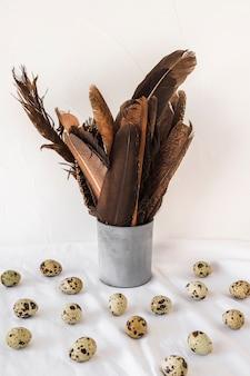 Набор пасхальных перепелиных яиц возле черных перьев в банке на текстиле