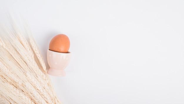 カップと小麦の束の近くのイースターチキン卵
